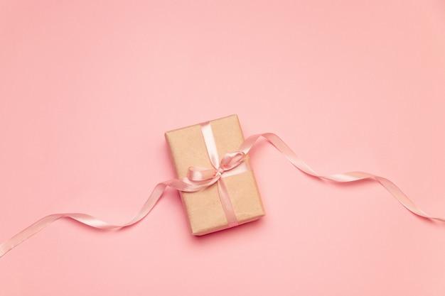 Boîte cadeau artisanale avec ruban noeud pastel rose sur toile rose