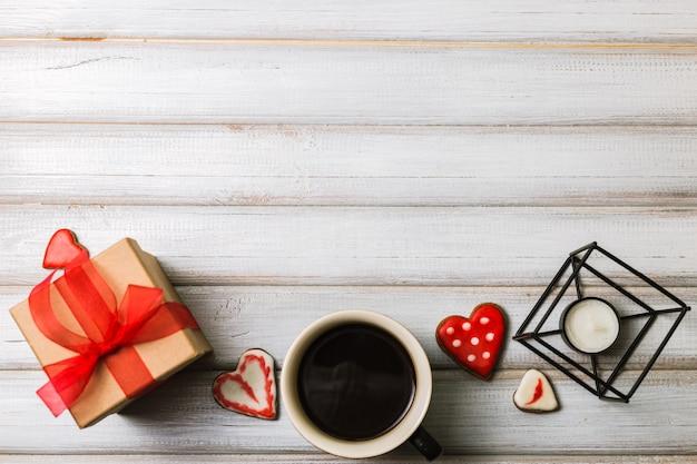 Boîte avec un cadeau aux biscuits de la saint-valentin en forme de cœur et des tasses de café noir