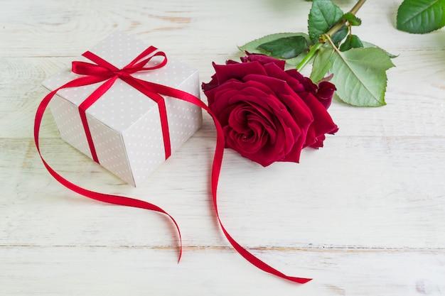 Boîte cadeau beige à pois avec ruban rouge et belles roses rouges sur fond en bois. carte de voeux pour les vacances.