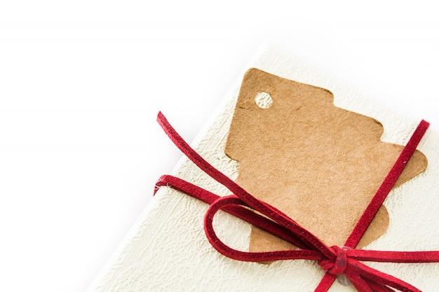 Boîte cadeau blanche et étiquette d'arbre de noël sur blanc. vue de dessus.