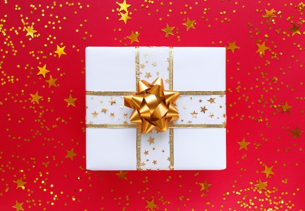 Boîte cadeau blanche avec noeud doré et étoiles o