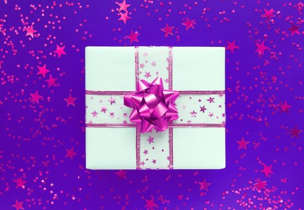 Boîte cadeau blanche avec noeud rose et étoiles