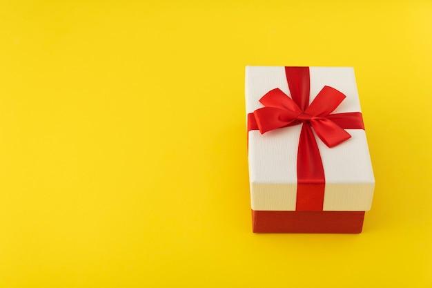 Boîte cadeau blanche avec noeud rouge, emballage cadeau festif. copiez l'espace. fond jaune.