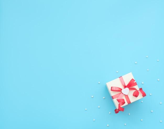 Boîte cadeau blanche avec ruban rouge et coeur blanc