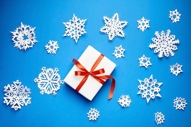 Boîte cadeau blanche avec ruban rouge et flocons de neige en papier sur fond bleu