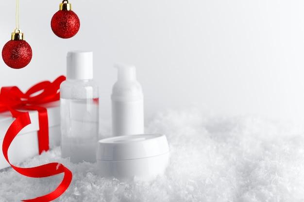 Boîte cadeau blanche avec ruban rouge et fond décoratif de boules scintillantes.