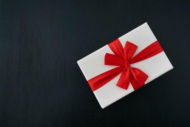 Boîte cadeau blanche avec ruban rouge sur fond noir. vue de dessus. emballage cadeau.