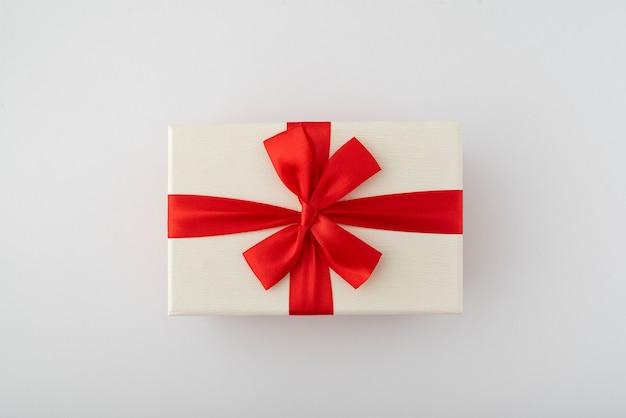 Boîte cadeau blanche avec ruban rouge et noeud sur blanc