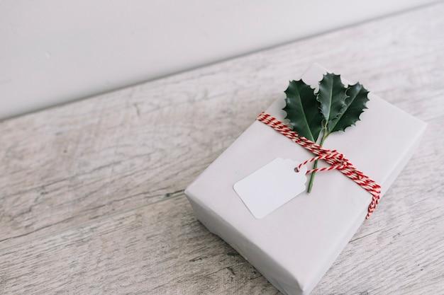 Boîte cadeau blanche avec des tracts sur une table en bois