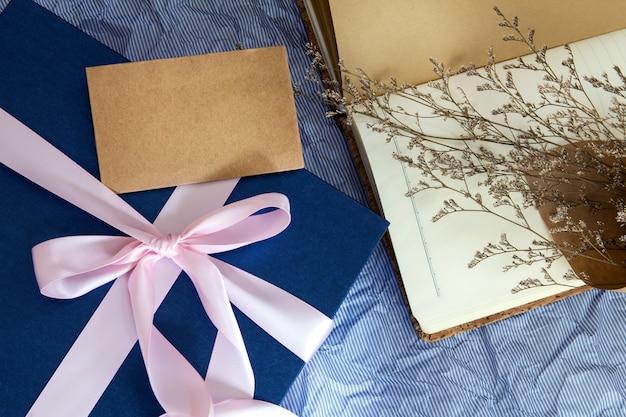 Boîte cadeau bleu foncé avec décoration de ruban avec livre et fleur sur papier bleu polka