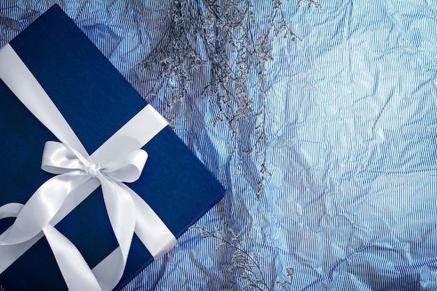 Boîte cadeau bleu foncé avec décoration de ruban sur papier bleu polka