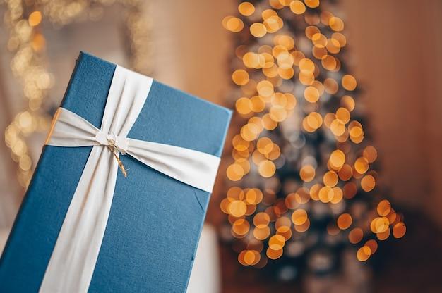 Boîte cadeau bleue contre l'arbre décoré de noël dans des couleurs dorées chaudes