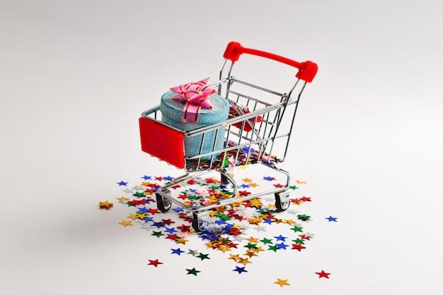 Boîte cadeau bleue avec noeud rose dans un panier et confettis sur fond blanc.