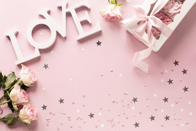 Boîte-cadeau ou boîte-cadeau et fleurs sur la vue de dessus de table rose.