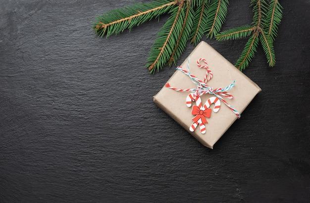 Boîte-cadeau et branches vertes d'aiguilles sur fond noir, fond de noël festif, espace copie
