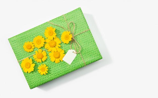 Boîte cadeau ou cadeau avec étiquette vierge et fleurs de marguerite sur blanc. copiez l'espace vue de dessus.