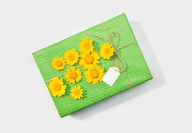 Boîte cadeau ou cadeau avec étiquette vierge et fleurs de marguerite sur blanc. vue de dessus.