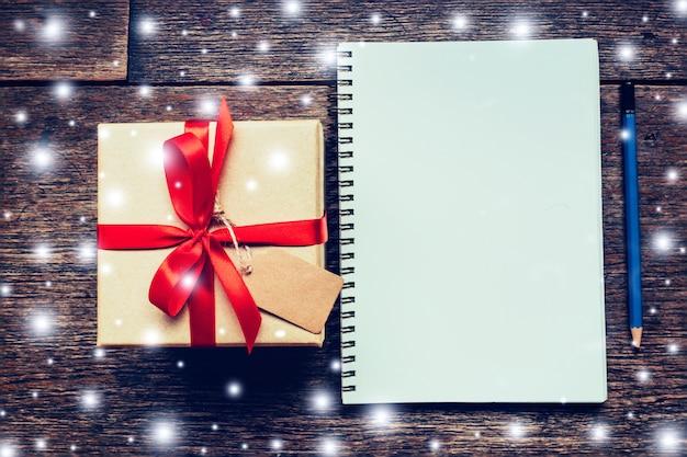 Boîte cadeau et cahier brun, crayon à la neige blanche sur fond de carton en bois avec espace.