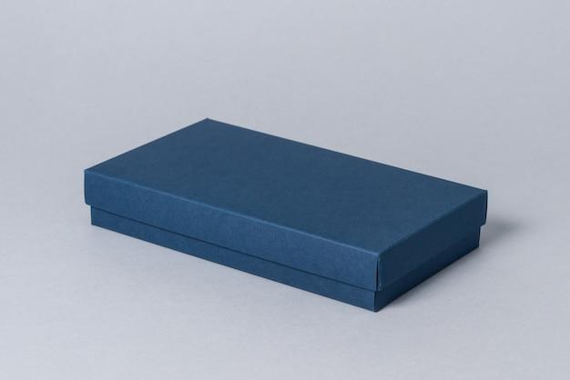 Boîte cadeau en carton bleu avec couvercle, sur fond gris