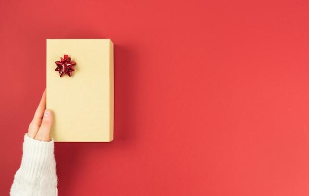 Boîte cadeau en carton avec des décorations sur fond rouge. saint valentin