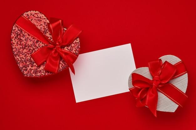 Boîte-cadeau de choix variés en forme de coeur avec un ruban rouge sur une table rouge. concept de la saint-valentin vue de dessus à plat avec espace de copie.