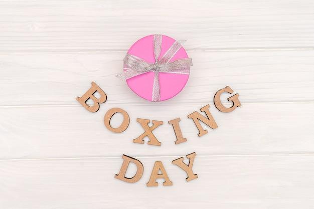 La boîte cadeau ci-dessus est attachée avec un ruban avec des mots boxing day sur bois blanc