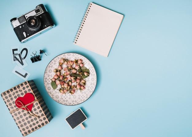 Boîte cadeau avec coeur d'ornement, appareil photo, bloc-notes et fleurs sur une assiette