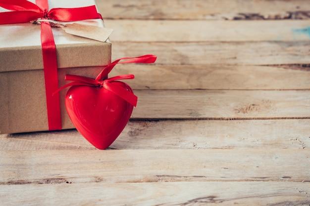 Boîte cadeau et coeur rouge sur table en bois avec espace