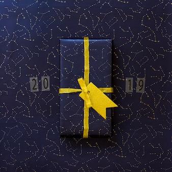 Boîte-cadeau dans l'emballage avec étiquette près des comprimés avec des chiffres