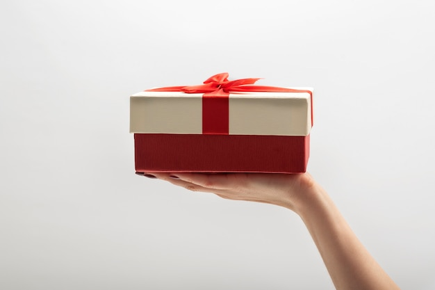 Boîte-cadeau dans la paume sur mur blanc