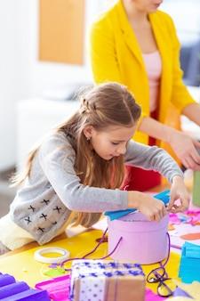 Boîte cadeau de décoration. écolière avec une belle coiffure se sentant occupée à décorer une boîte présente à la leçon
