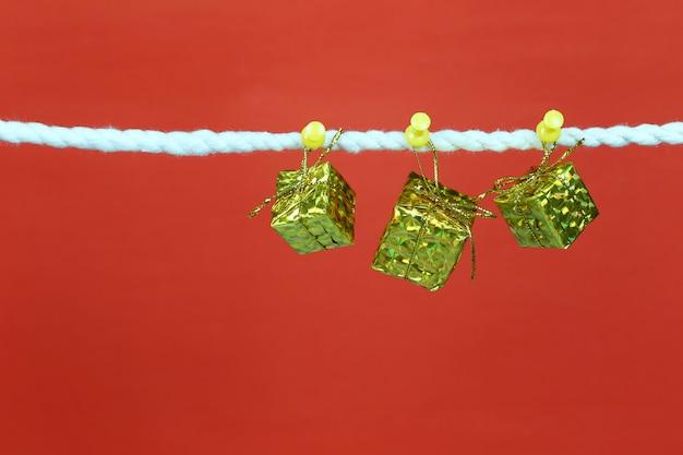Une boîte cadeau dorée est suspendue à la corde à linge.