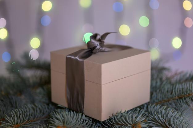 Une boîte avec un cadeau du nouvel an se trouve sur une branche d'arbre de noël dans le contexte d'une guirlande étincelante.