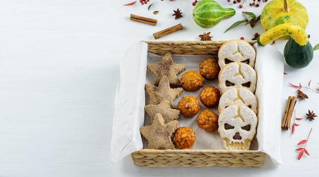 Une boîte cadeau écologique avec des bonbons d'halloween présente des panelles de piones biscuits à la cannelle et des citrouilles décoratives sur la table.