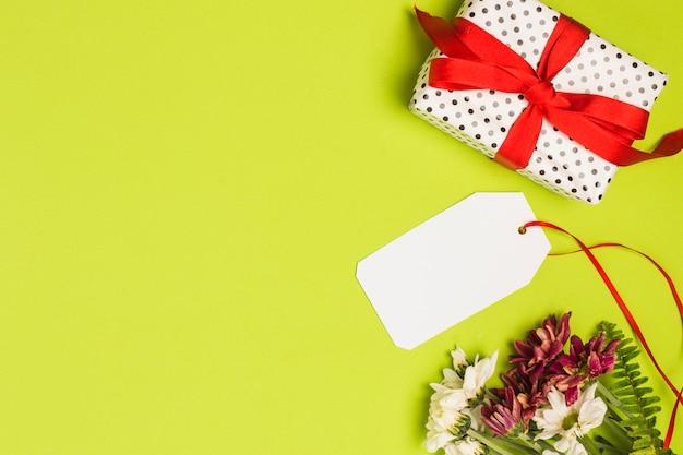 Boîte cadeau emballé à pois avec étiquette vierge et bouquet de fleurs sur fond vert