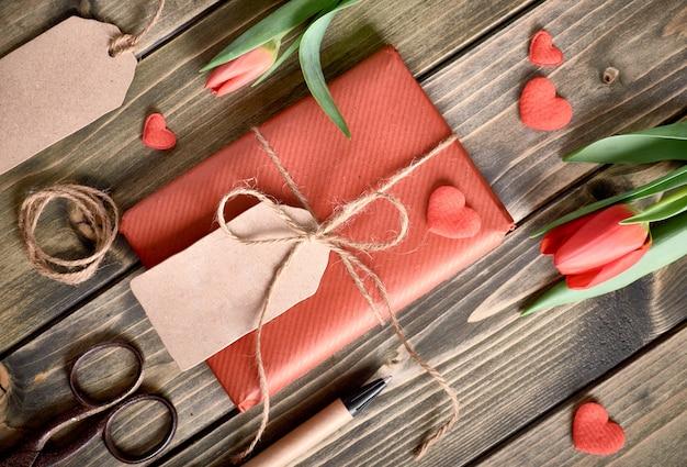 Boîte cadeau emballée, cordon, ciseaux, étiquettes et coeurs décoratifs sur bois