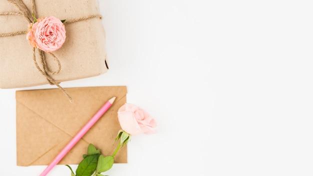 Boite cadeau; enveloppe; crayon de couleur et fleur rose sur fond blanc
