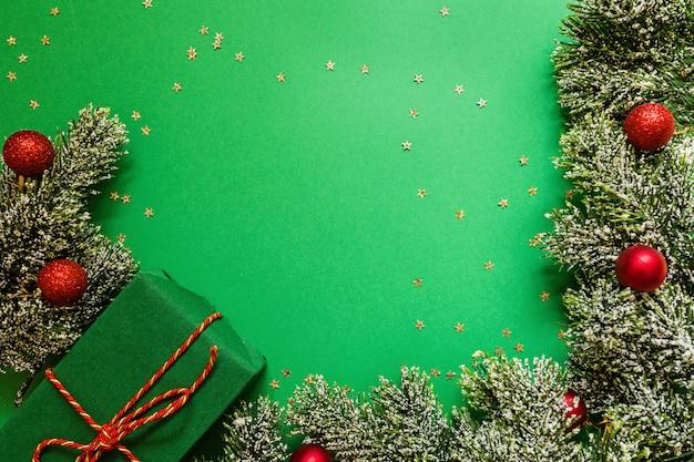 Boîte de cadeau enveloppé de noël et des branches d'arbres sur fond vert avec des confettis