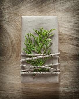 Boîte cadeau fait main avec branche de thuya vert sur planche de bois