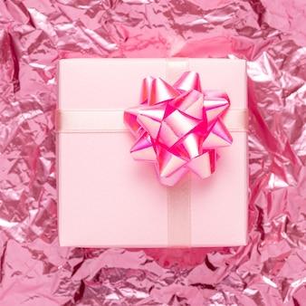 Boîte-cadeau sur fond d'aluminium froissé rose