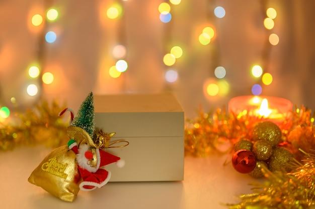 Une boîte avec un cadeau sur fond de bougie allumée et une guirlande lumineuse de couleur chaude.