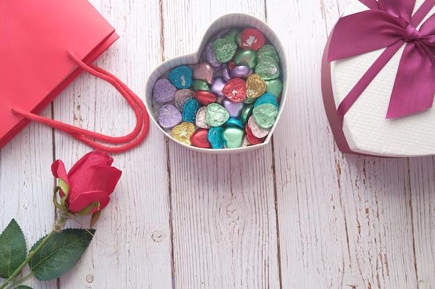 Boîte-cadeau en forme de coeur avec des bonbons sur la table.