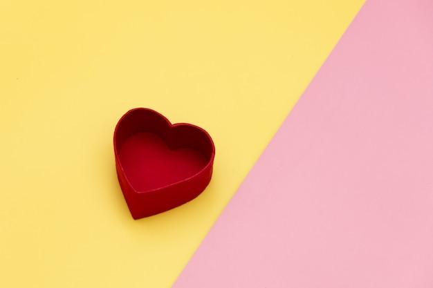 Boîte cadeau en forme de coeur sur fond jaune et rose