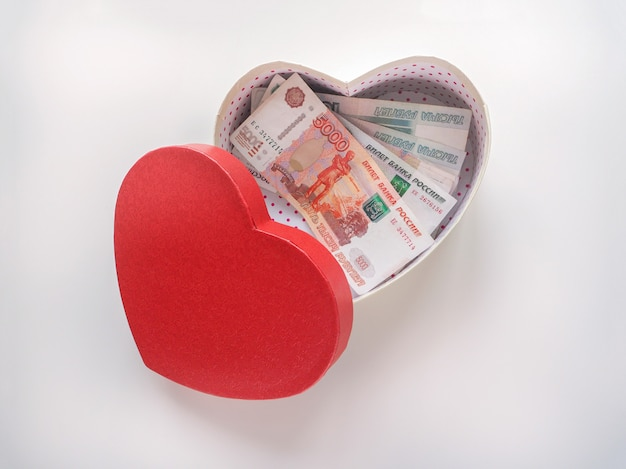 Boîte-cadeau en forme de coeur avec des roubles russes sur un tableau blanc