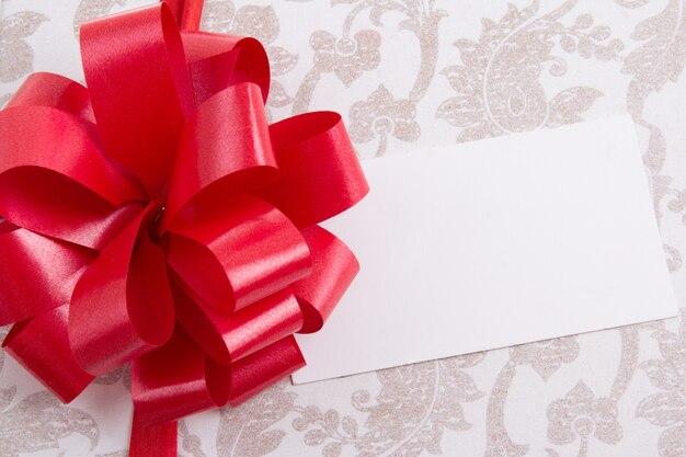 Boîte-cadeau avec grand arc rouge et carte de voeux vide