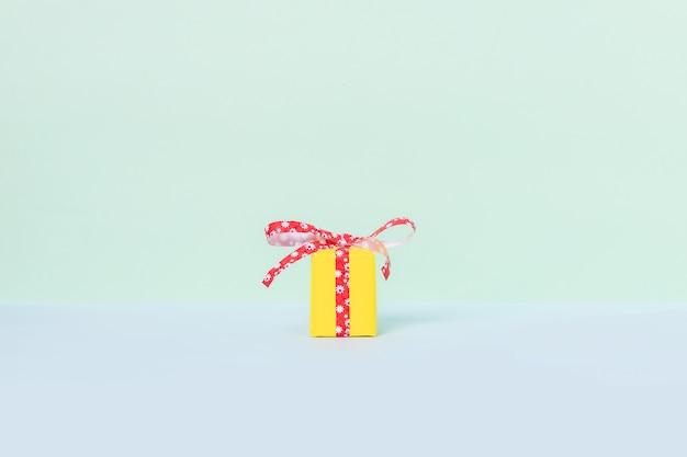 Boîte cadeau jaune avec ruban rouge sur fond pastel.