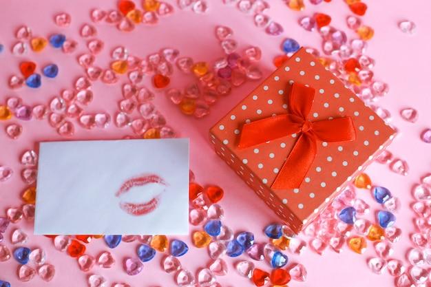 Une boîte-cadeau et une marque de baiser sur l'enveloppe avec des billes sur fond rose