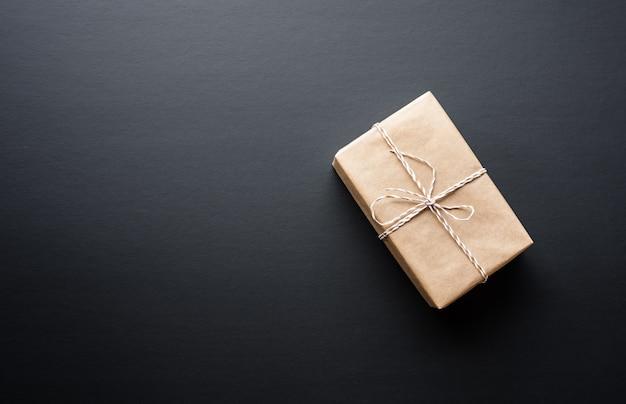Boîte cadeau marron dans un style bricolage sur fond sombre