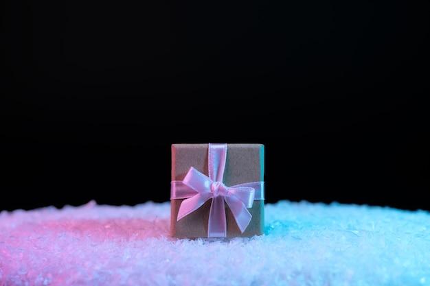 Boîte-cadeau sur la neige dans des couleurs holographiques dégradées audacieuses et vibrantes