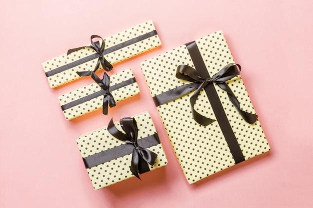 Boîte de cadeau de noël avec un arc noir sur rose